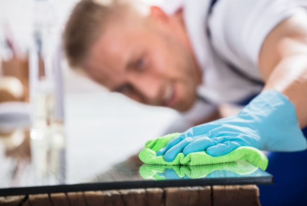 Close-up Of A Worker Cleaning Desk With Cloth